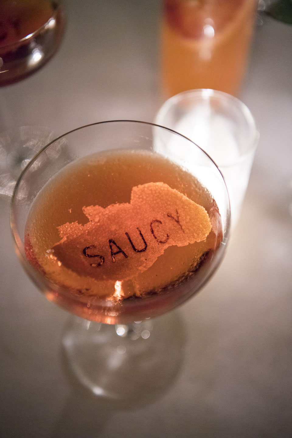 A cocktail garnished with an orange zest branded with the word saucy