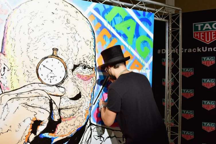 TAG Heuer's Art Provocateur Alec Monopoly spray-paints a liking of the brand's CEO Jean-Claude Biver.