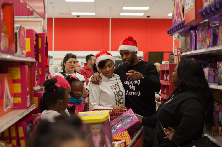 Chris and his wife, Jada, helping kids shop at the 3rd Annual Holiday Takeover