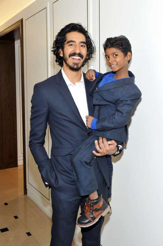 Actors Dev Patel (L) and Sunny Pawar wearing Burberry