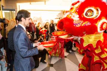 Lucky Dragon Hotel & Casino Grand Opening – 12.3.16 – COO Dave Jacoby offers a tray of persimmons to a lion at the Lucky Dragon grand opening