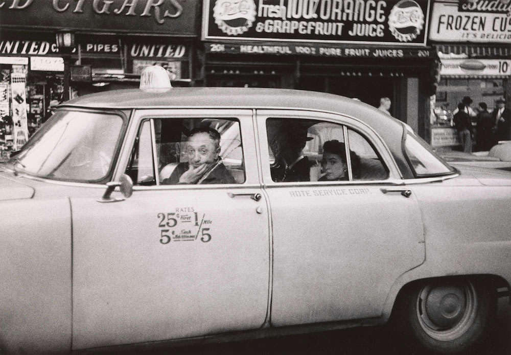 Diane Arbus, Taxicab driver at the wheel with two passengers, N.Y.C.1956