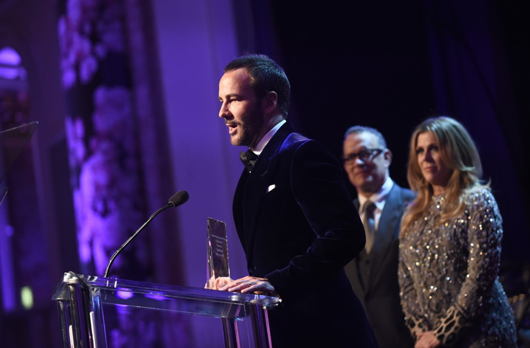 "Honoree Tom Ford accepts the Courage Award from honorary co-chairs Rita Wilson and Tom Hanks onstage during WCRF's ""An Unforgettable Evening"""