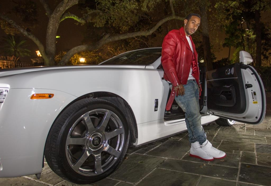 Ludacris reclines on one of the Rolls-Royce cars on display| photos by Thaddaeus McAdams