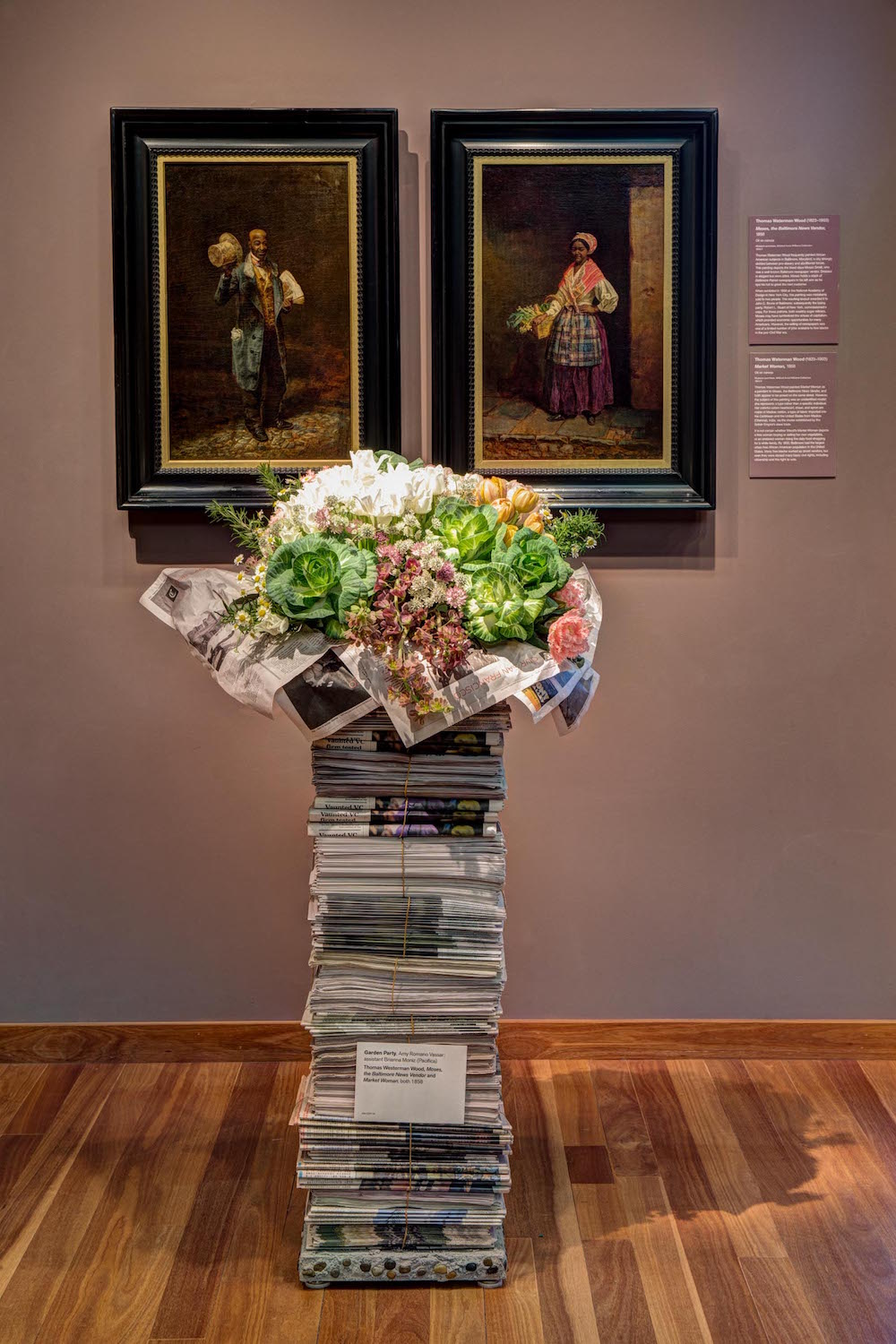 """2015 floral display by Garden Party. Artwork: Thomas Westerman Wood, (left) """"Moses, the Bal-timore News Vendor,"""" 1858; (right) """"Market Woman,"""" 1858"""