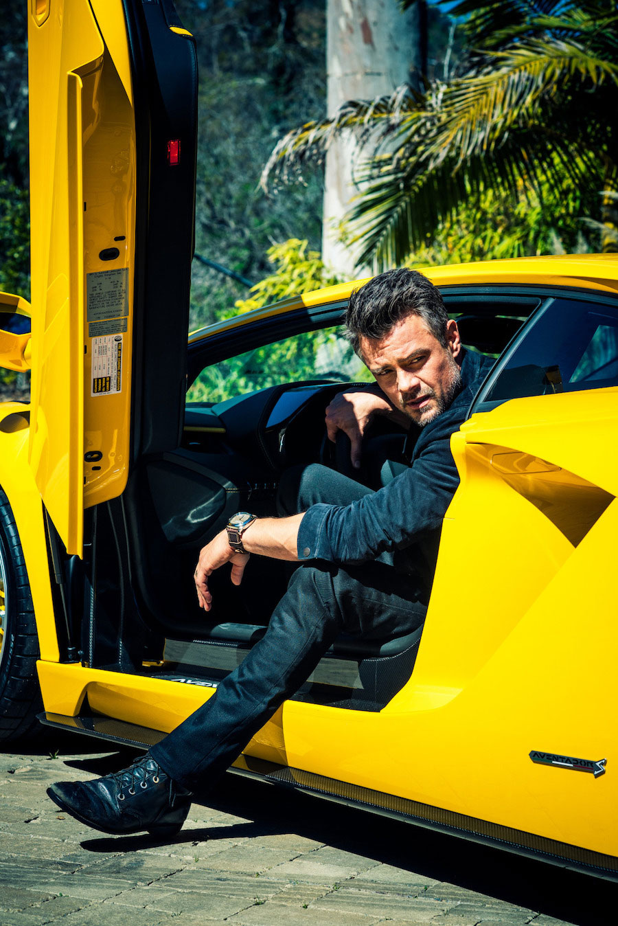Duhamel wears a John Varvatos shirt and jacket, Nudie Jeans black jeans, Panerai watch, and his own shirt and shoes while sitting in the driver's seat of the 2017 Lamborghini Aventador S Coupé.