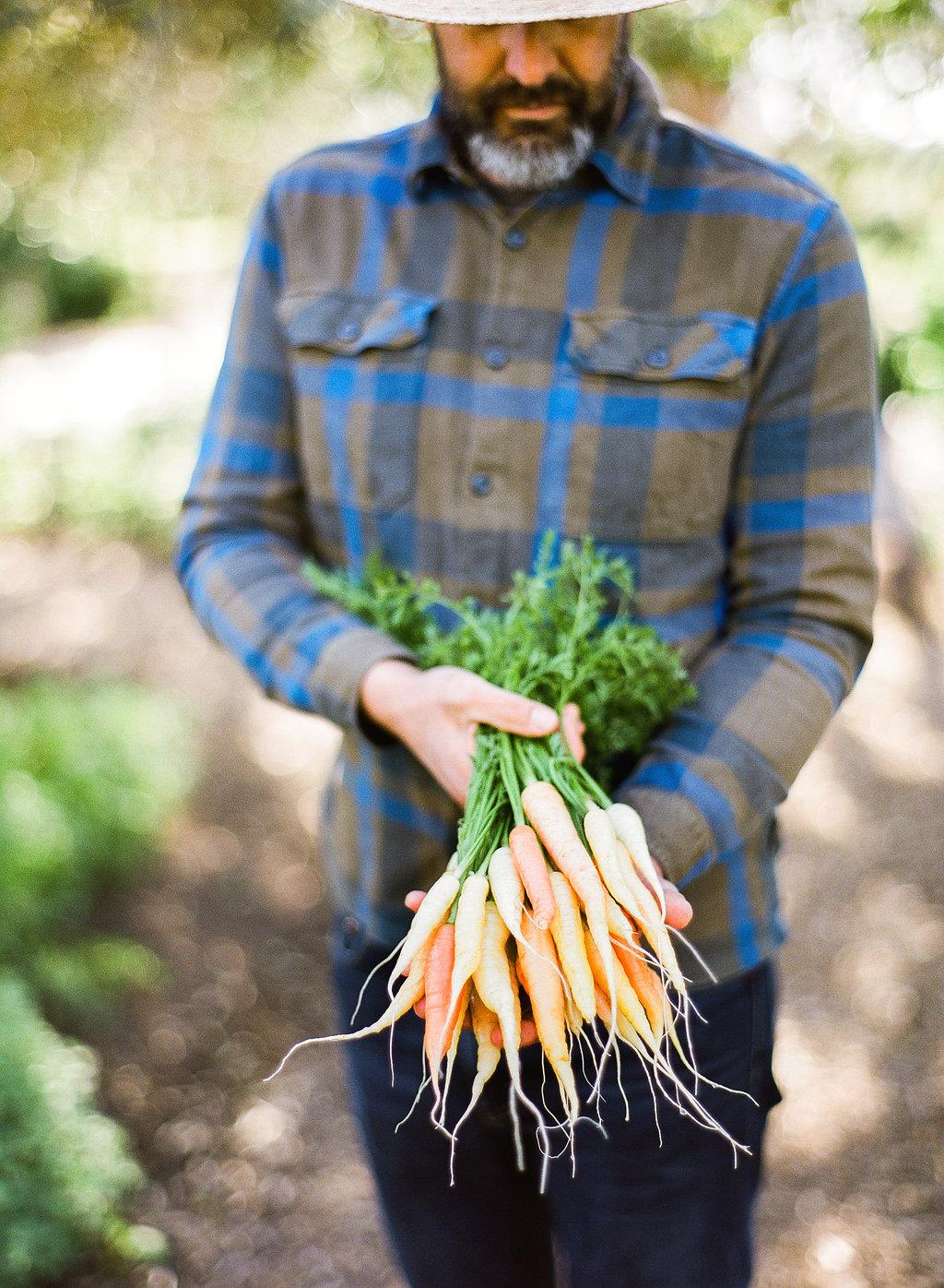 Farmer T with just-harvested carrots