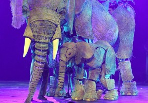 Puppeteers perform with an elephant puppet named Queenie (left) and puppeteer Luke Chadwick-Jones operating a baby elephant puppet named Peanut.