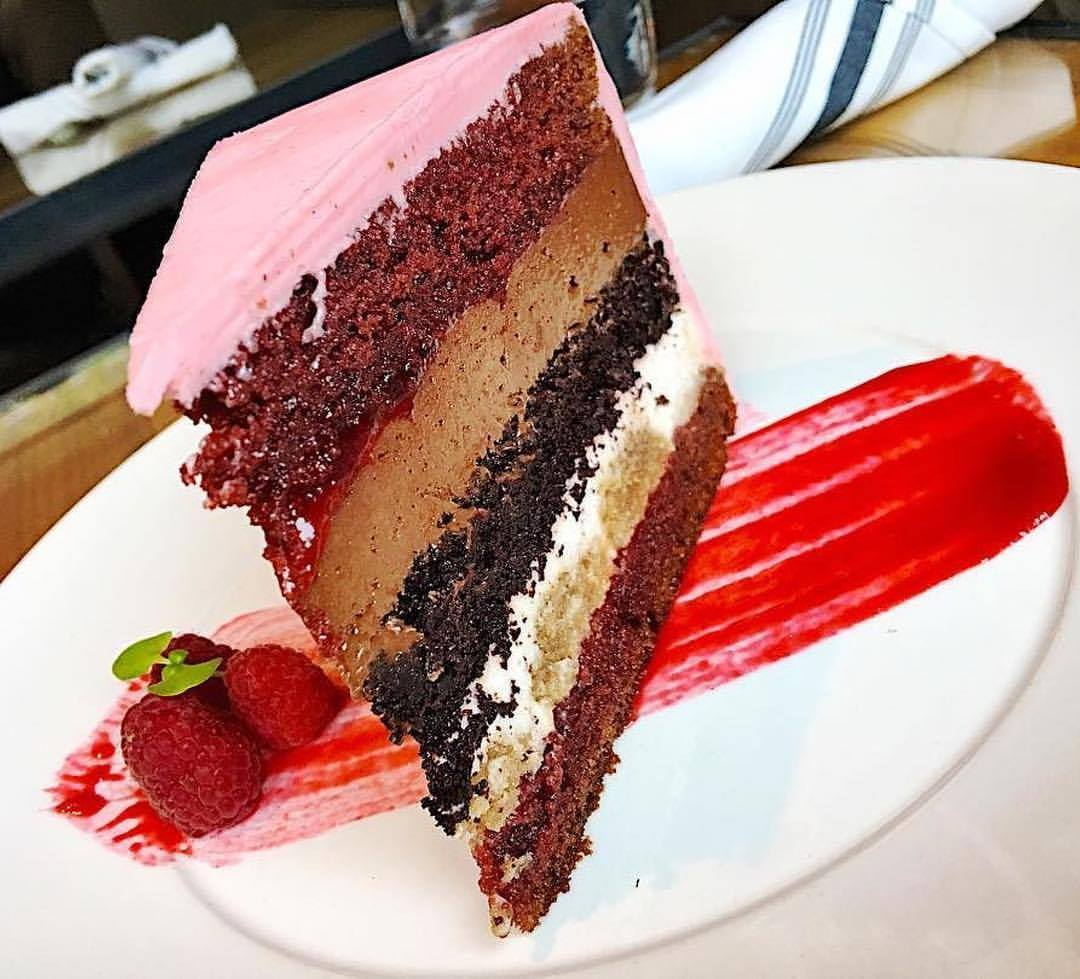 Pastry chef Lori Baker's six layer cake (made of red velvet, devils food, chocolate mousse, tiramisu, raspberry jam, and raspberry buttercream) was recently on the menu at Bluestem Brasserie.