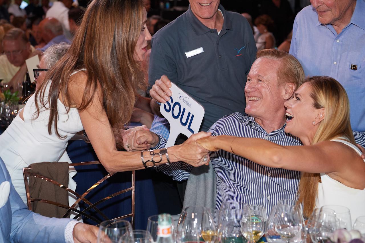 Valerie Garjiulo, of Garjiulo Vineyards, shakes the hands of the winners of her auction lot, Rick Jones standing right