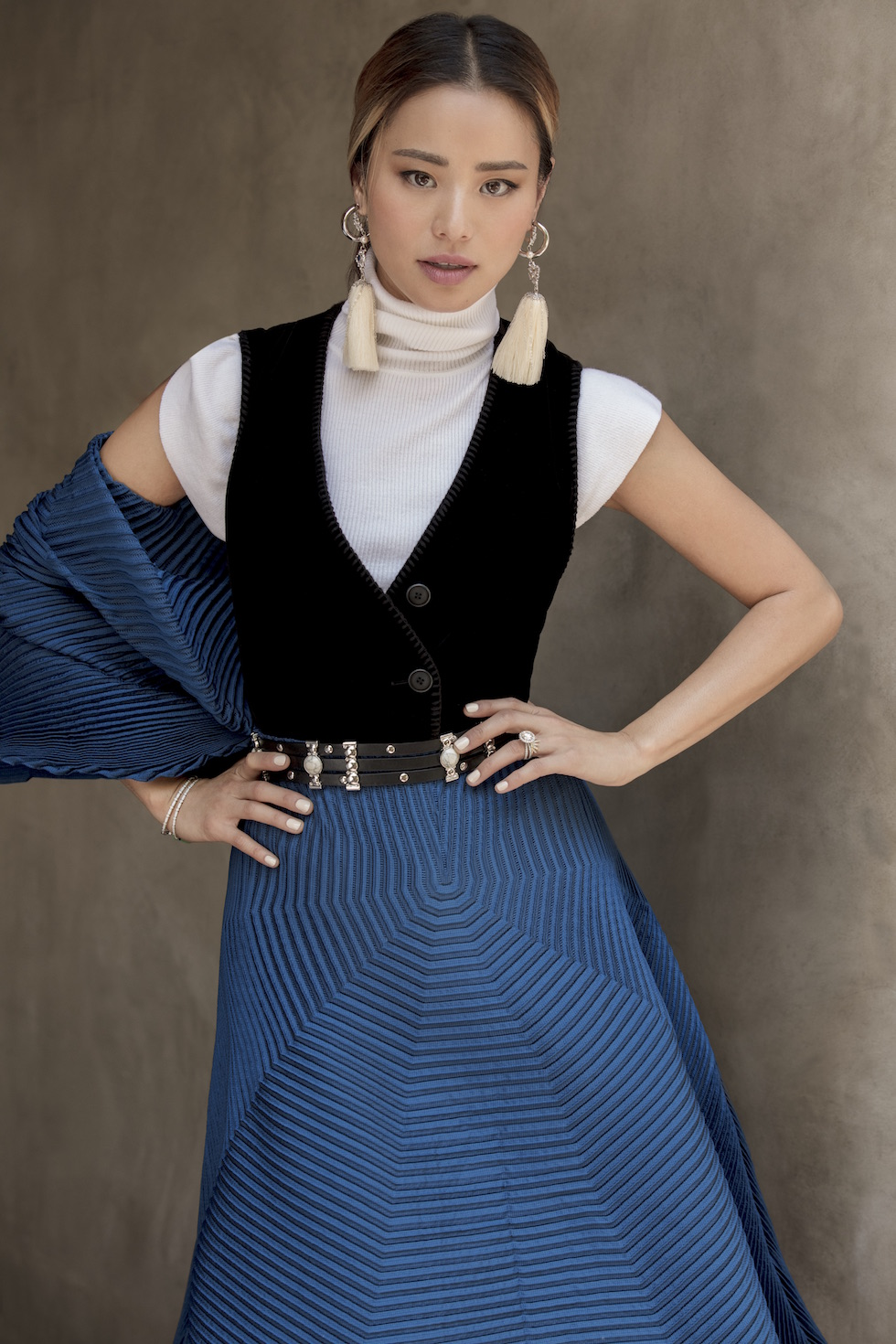 Chung wears an Issey Miyake skirt and shawl, A.L.C top, Giorgio Armani vest, the stylist's personal belt, O2 by Oxygen White Tassel earrings, A.V Max silver joops, and a Dana Rebecca White gold bracelet.