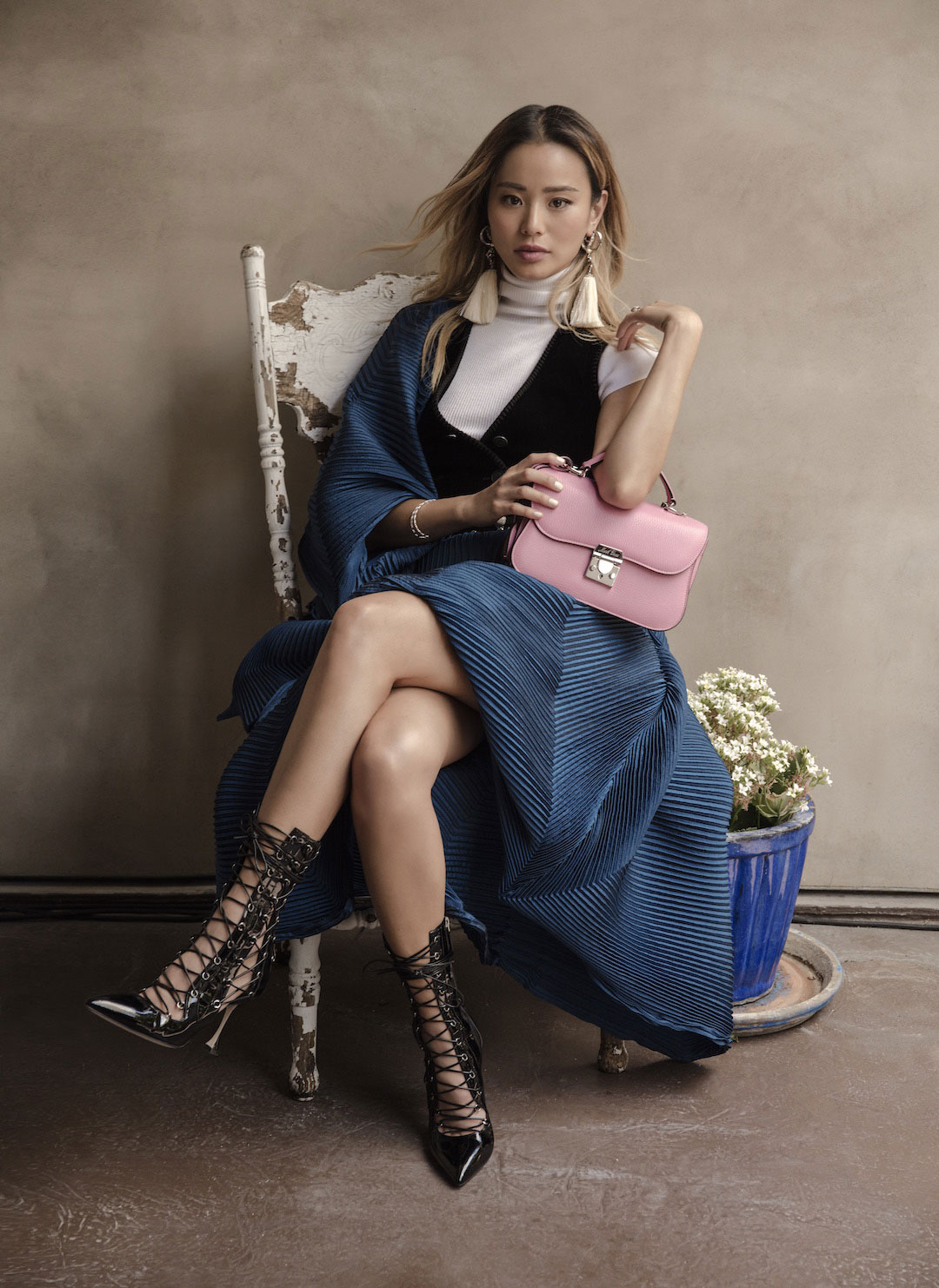Chung sitting pretty in an Issey Miyake skirt and shawl, A.L.C top, Giorgio Armani vest and, Liudmila Boots. She holds a Mark Cross purse and is wearing O2 by Oxygen White Tassel earrings, A.V Max silver joops, and a Dana Rebecca White gold bracelet.