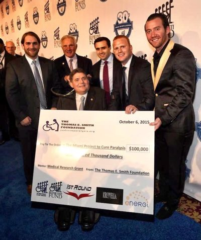 Thomas Smith, Chris Smith, and Teague Egan presenting the $100,000 donation to Marc Buoniconti at the 30th Great Sports Legends Dinner in 2015