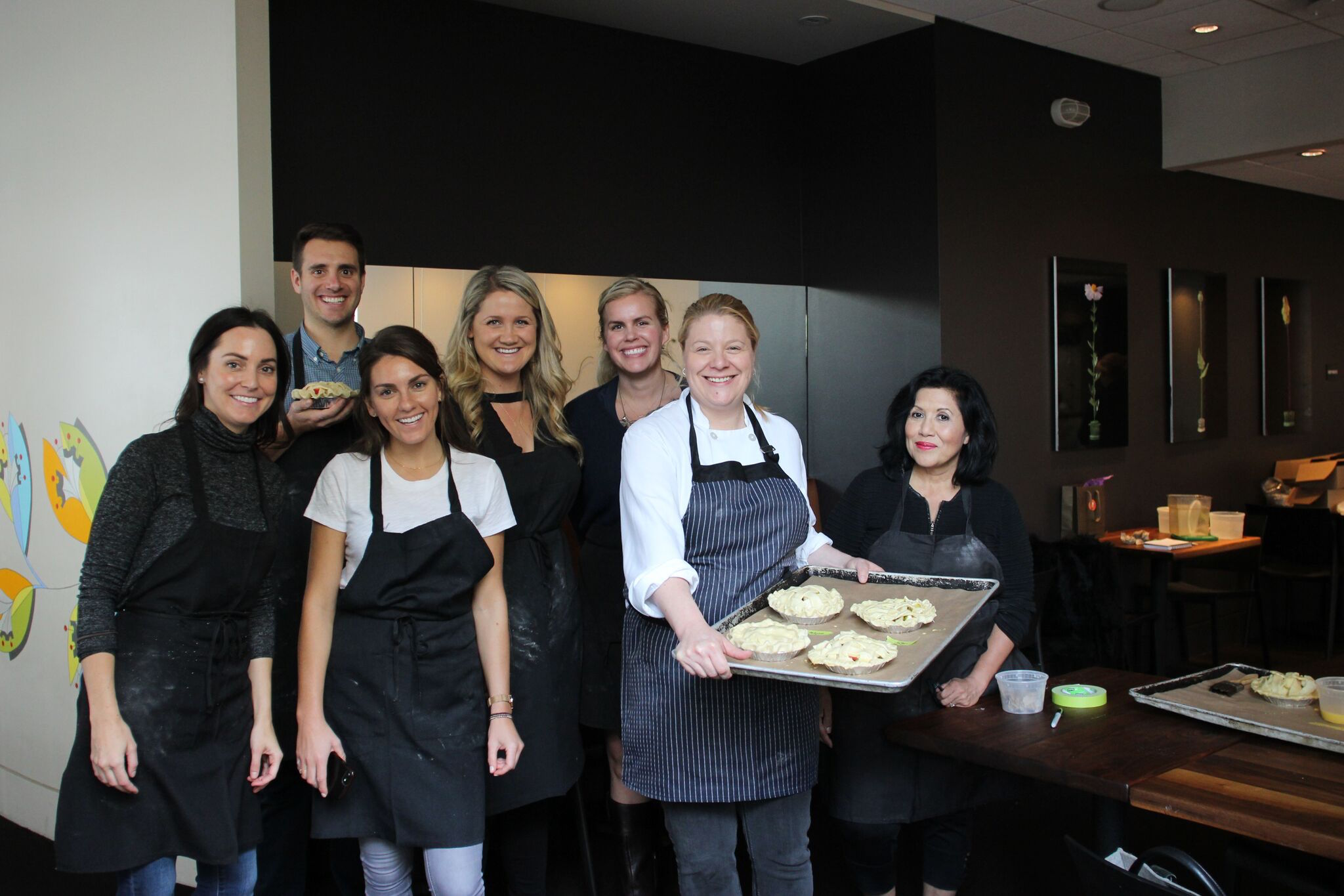 Lori Baker, holding the tray, surrounded by her students at a pie making class