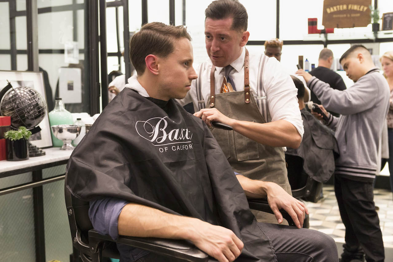 A man gets a hair trim at the Baxter of California pop up at Banana Republic