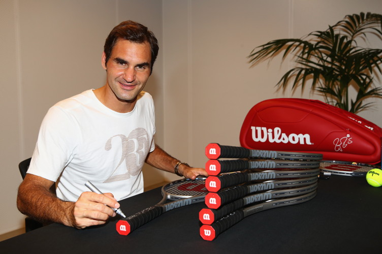 Roger Federer of Switzerland signs twenty Wilson Pro Staff commemorative tennis rackets to be sold for charity after winning his 20th grand slam title against Marin Cilic of Croatia on day 14 of the 2018 Australian Open at Melbourne Park on January 28, 2018 in Melbourne