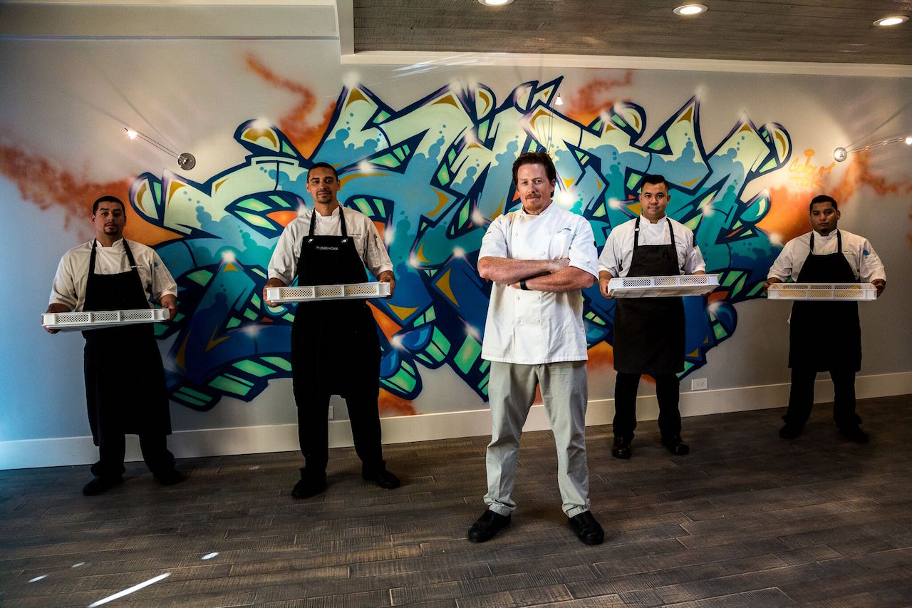 The Pasta Armellino team poses in front of a Chris Kondo graffiti mural