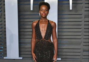 Lupita Nyong'o attends the 2018 Vanity Fair Oscar Party at Wallis Annenberg Center for the Performing Arts wearing Armani Prive and Forevermark Diamonds