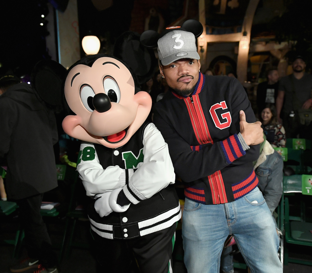 "ANAHEIM, CA - MARCH 07: Mickey Mouse (L) and Chance The Rapper attend the launch of ""Mickey the True Original"" campaign in celebration of Mickey's 90th anniversary with a fashion show featuring a Mickey-inspired collection by Opening Ceremony at Disneyland on March 7, 2018 in Anaheim, California. (Photo by Neilson Barnard/Getty Images for Disney)"