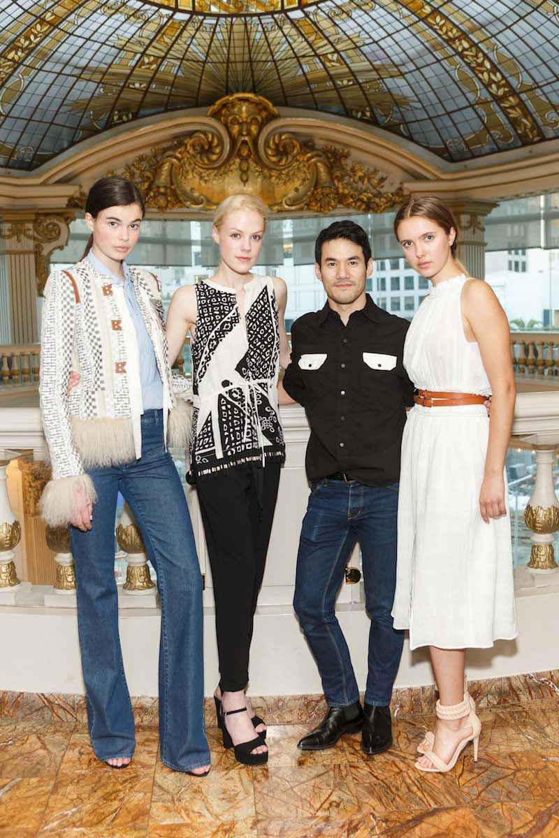 Joseph Altuzarra poses with models wearing his designs