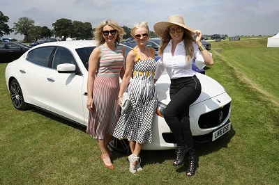 TETBURY, ENGLAND - JUNE 10: Maserati Royal Charity Polo Trophy 2018 – (R-L) Carol Vorderman, Lisa Maxwell and guest with the Maserati Quattroporte attend the Maserati Royal Charity Polo Trophy 2018 at Beaufort Polo Club on June 10, 2018 in Tetbury, England.