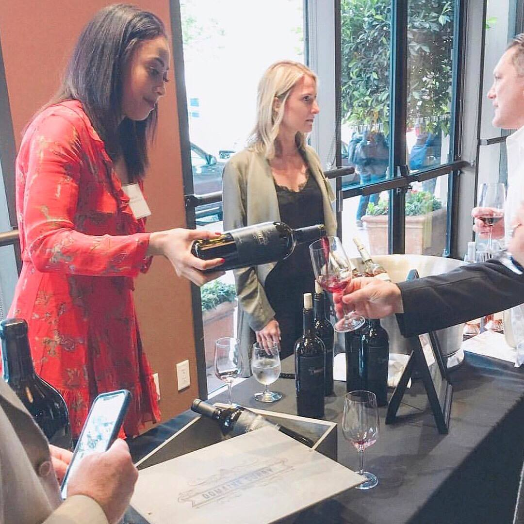 Sydel Curry, left, pouring her wine at the recent reception