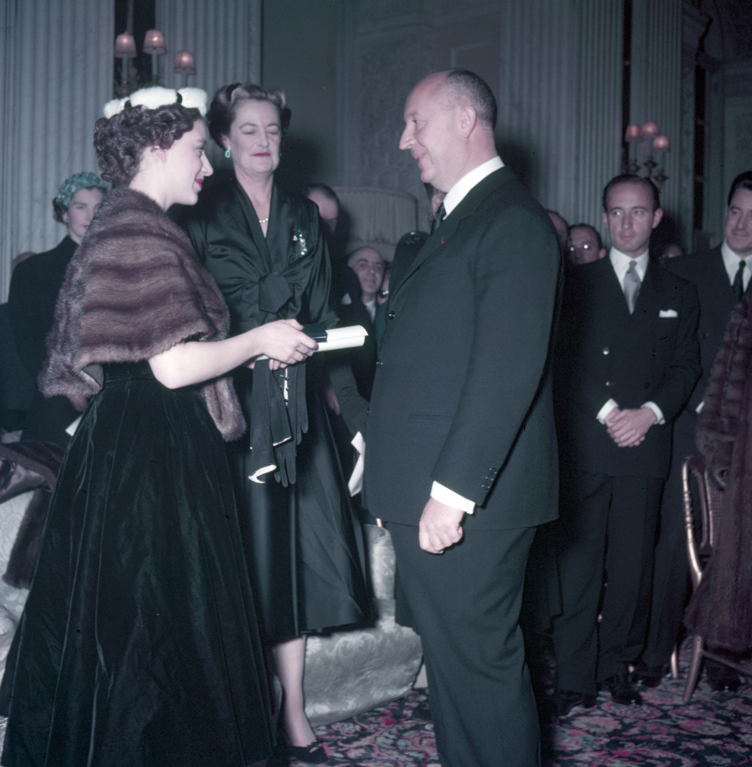 Princess Margaret (left), with the Duchess of Marlborough behind, presents Christian Dior with a scroll entitling him to Honorary Life Membership of the British Red Cross after the presentation of his Winter Collection at Blenheim Palace on 3rd November 1954.