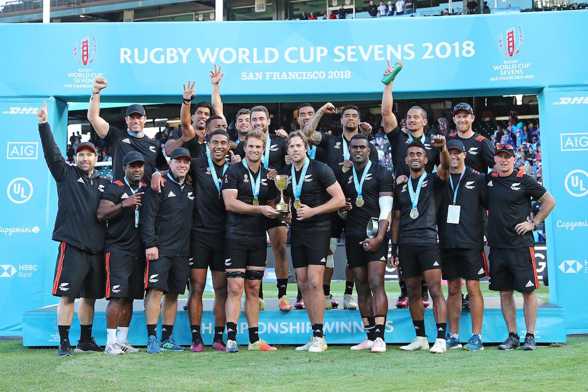 New Zealand players and staff celebrate the successful defense of their title