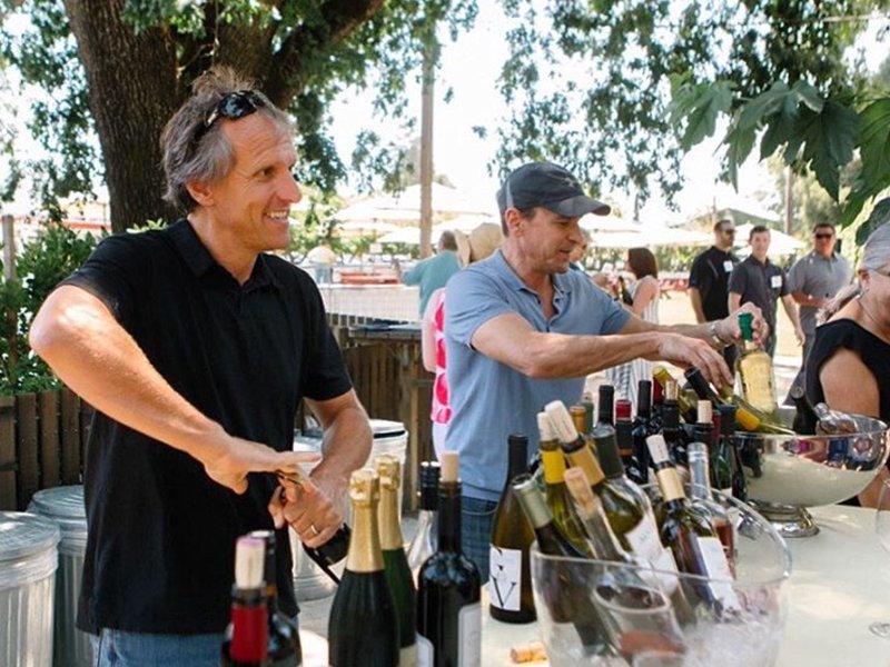 Joel Gott, left, opens wine bottles at an event