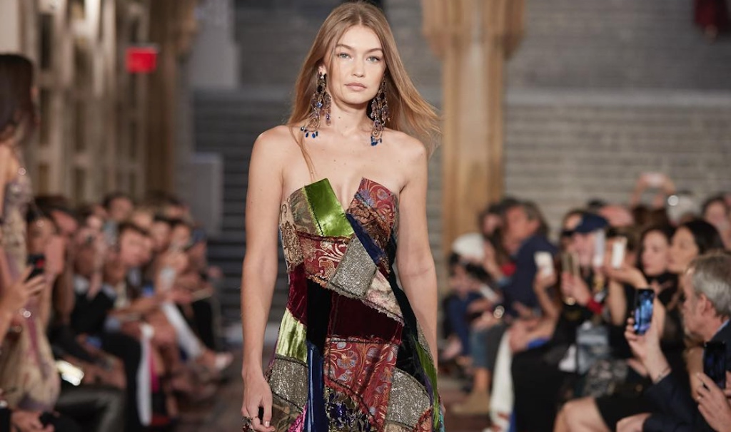 Gigi Hadid wearing a handmade patchwork gown of 132 separate patches united by zigzag stitching and embroidery showcasing a patchwork American Flag.