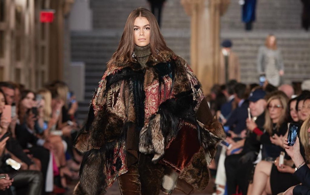 Kaia Gerber wearing a patchworked Italian shearling cape on the runway.