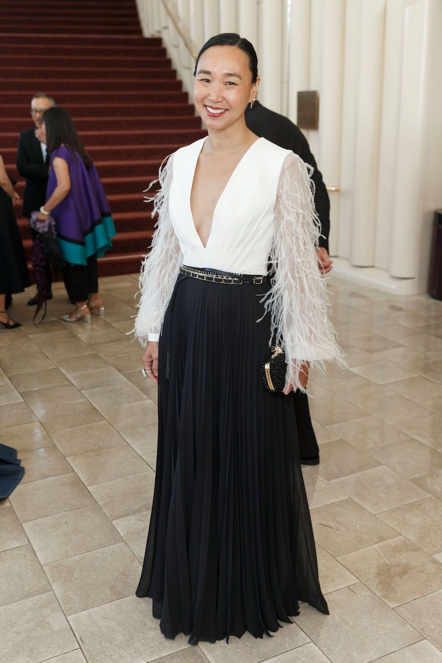"Kinney says, ""I loved the detail of Carolyn Chang's look with the low V and the white feathers."""