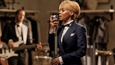 Janelle Monáe with blonde hair singing on microphone
